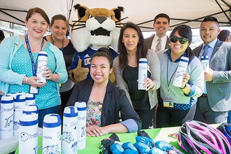 Staff members pose with campus mascot Rufus Bobcat and sustainable water bottles.