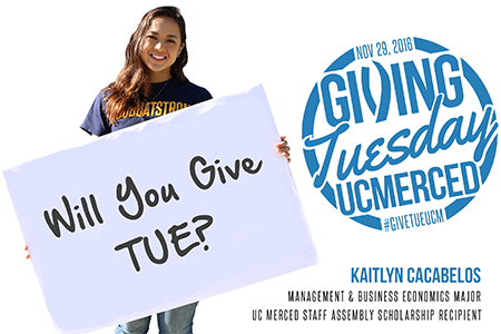 """A female student wearing a Bobcat Strong T-shirt holds a sign that reads, """"Will You Give Tue?"""" in reference to Giving Tuesday."""