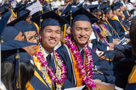 Students in blue caps and gowns smile at the camera during graduation.
