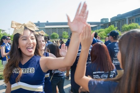 Students high-five each other as they participate in the Scholar's Lane Bridge crossing event at UC Merced.