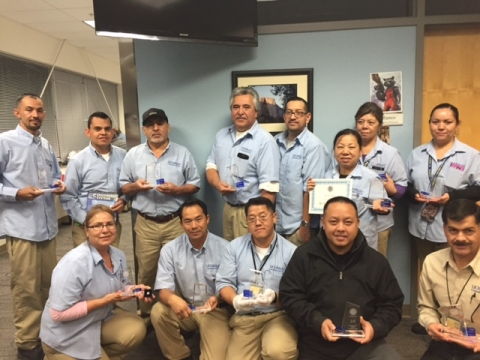 Members of the custodial staff pose with their service awards.