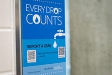 Signage shows restroom visitors how they can report water leaks using their smartphones.