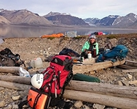 """Professor Marilyn Fogel makes coffee on the shores of Billefjorden, Svalbard, nearby the Ebbadalen """"blueberry"""" rock outcrop."""