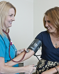 A nurse monitors a patient's blood pressure reading.