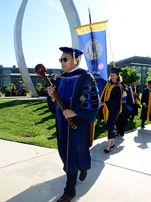Academic Senate Chair and Engineering Professor Jian-Qiao Sun carries the mace at Commencement 2015.