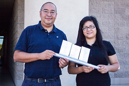 Professor Gerardo Diaz, left, and student Azucena Robles display a model of just a few of the mini-channel panels that can make up a larger solar collector.