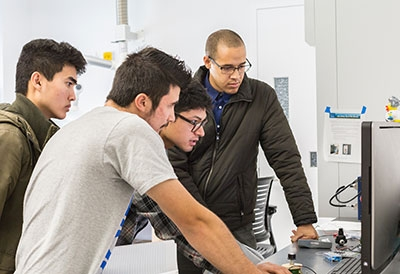Derek Brigham, Jonny Nguyen and Marek Abarca work in Professor Abel Chuang's engineering lab.