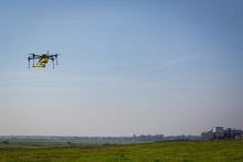 Image of a hovering drone with the UC Merced campus in the background.