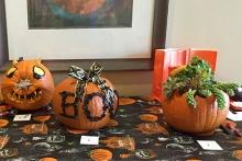 Three decorated Halloween pumpkins on display.