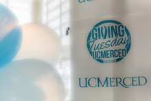 Balloons and a banner promote UC Merced's Giving Tuesday campaign.