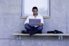 A man sits outside of a campus building with a laptop.