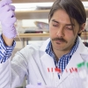 Professor Fabian V. Filipp wears a white lab coat while conducting research in a lab.