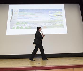 Chancellor Dorothy Leland on stage with the Vision and Change Alignment map projected on a screen behind her.