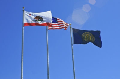 Flags of the State of California, United States and University of California wave in the wind.