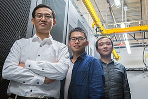 Professor Dong Li and students Yingchao Huang, center, and Luanzheng Guo work on supercomputing efficiency.