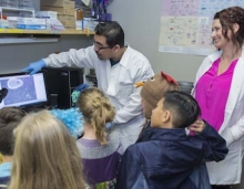 Two UC Merced faculty members show elementary students information on a computer.
