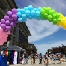 A rainbow-colored balloon  arch decorates Scholars Lane outside of Kolligian Library.