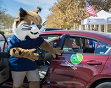 Campus mascot Rufus Bobcat stands next to one of new Zipcars in use at UC Merced.