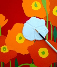 An unglazed ceramic poppy is shown on a colorful background.