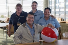 Four staff members from facilities pose with a beach ball.
