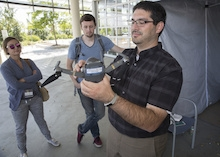 Staff members watch as a man holds and discusses a drone.