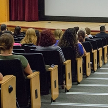 Employees sit in an auditorium waiting for a program to start.
